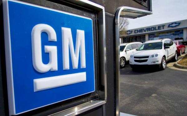 Logo de General Motors en una de sus instalaciones donde se ven también unas camionetas