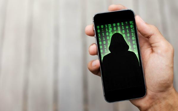 Silueta de espía en la carátula de un teléfono móvil sujetado con una mano