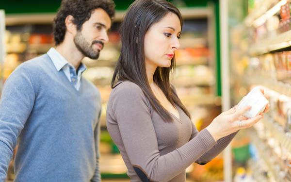 Consumidores revisando etiquetado de un producto en el súpermercado