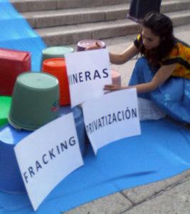 """Instalación al pie del Ángel de la Independencia con cubetas y las leyendas """"Fracking"""", """"Mineras"""" """"Privatización"""""""