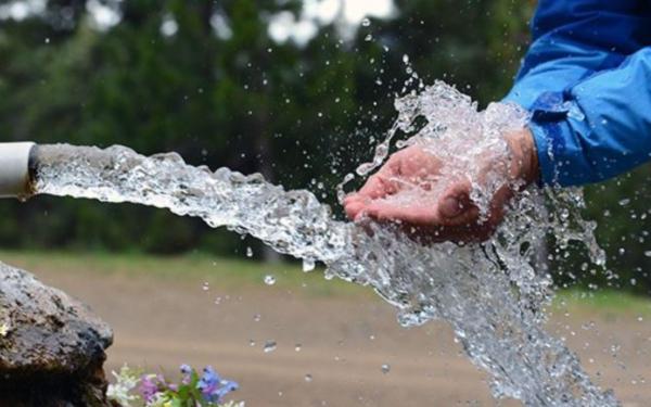 Manos juntas conteniendo el vital líquido frente al chorro de agua