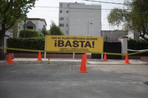 Manta colocada en la fachada de la AMIA que dice: Más de 24,000 mexicanos decimos ¡BASTA! Exigimos a la industria automotriz vender sólo autos seguros en México