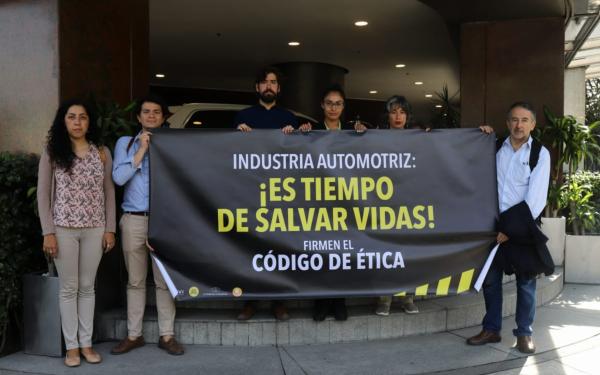 Imagen de integrantes de la organizaciones civiles con manta que dice Industria automotriz: ¡es tiempo de salvar vidas! Firmen el Código de Ética