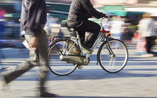 Un ciclista y un peatón en la vía pública