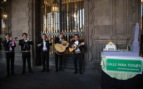 Mariachi cantando en entrada del Edificio del Ayuntamiento en el Zócalo de la CDMX y maqueta de una parte del Eje Central de la ciudad con las leyendas: Calle para tod@s, Coalición Cero Emisiones
