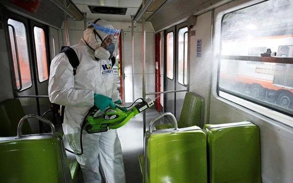 Persona sanitizando los interiores de un vagón del Metro