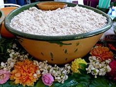 Jícara o plato hondo de barro con tejate en polvo sobre una mesa con flores