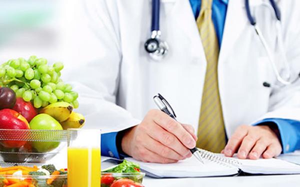 Nutriólogo escribiendo con frutas y verduras a un lado
