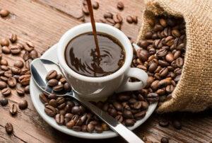 Café en una taza con granos de café alrededor