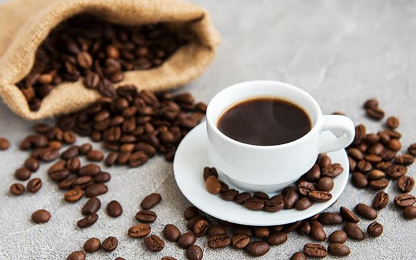 Café en granos esparcidos por una mesa, saliendo de un costalito, junto a una taza de café