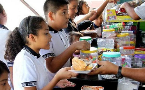Niñas y niños comprando alimentos en la cooperativa de la escuela