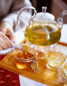 Miel de abeja, como endulzador, junto a tazas y jarra de té